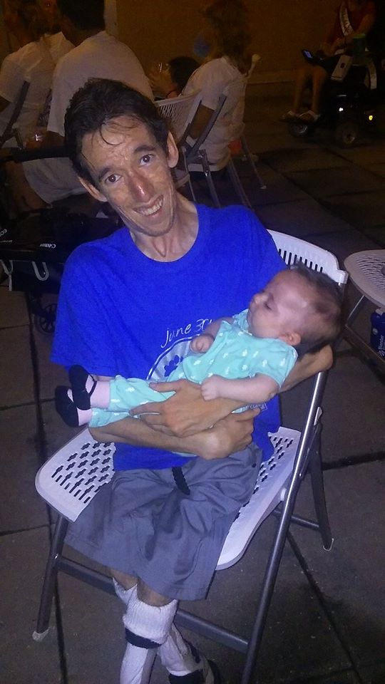 Photo of Marty holding a baby who also has Arthrogryposis.