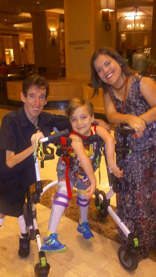 Photo of Marty and a young child and adult woman. All three have Arthrogryposiss. The child is using a a gait trainer device.