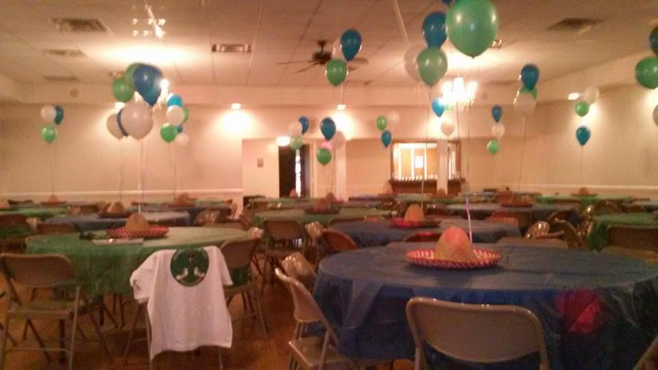 Photo of fundraiser event venue showing a number of circular tables covered in blue and green plastic. There are balloons of various colors and other decorations throughout the room.